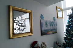 Espejo con marco de moldura en acabado pan de bronce.