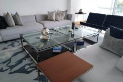 Mesa con estructura de acero inoxidable y tablero de vidrio.