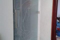 Puerta con accesorios  de acero inoxidable y vidrio con diseño personalizado.
