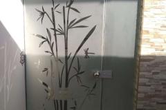 Puerta pivotante con vidrio templado. Diseño arenado